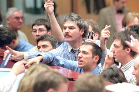 Traders signal at the Frankfurt stock exchange 20 March, where the DAX index broke up through the...